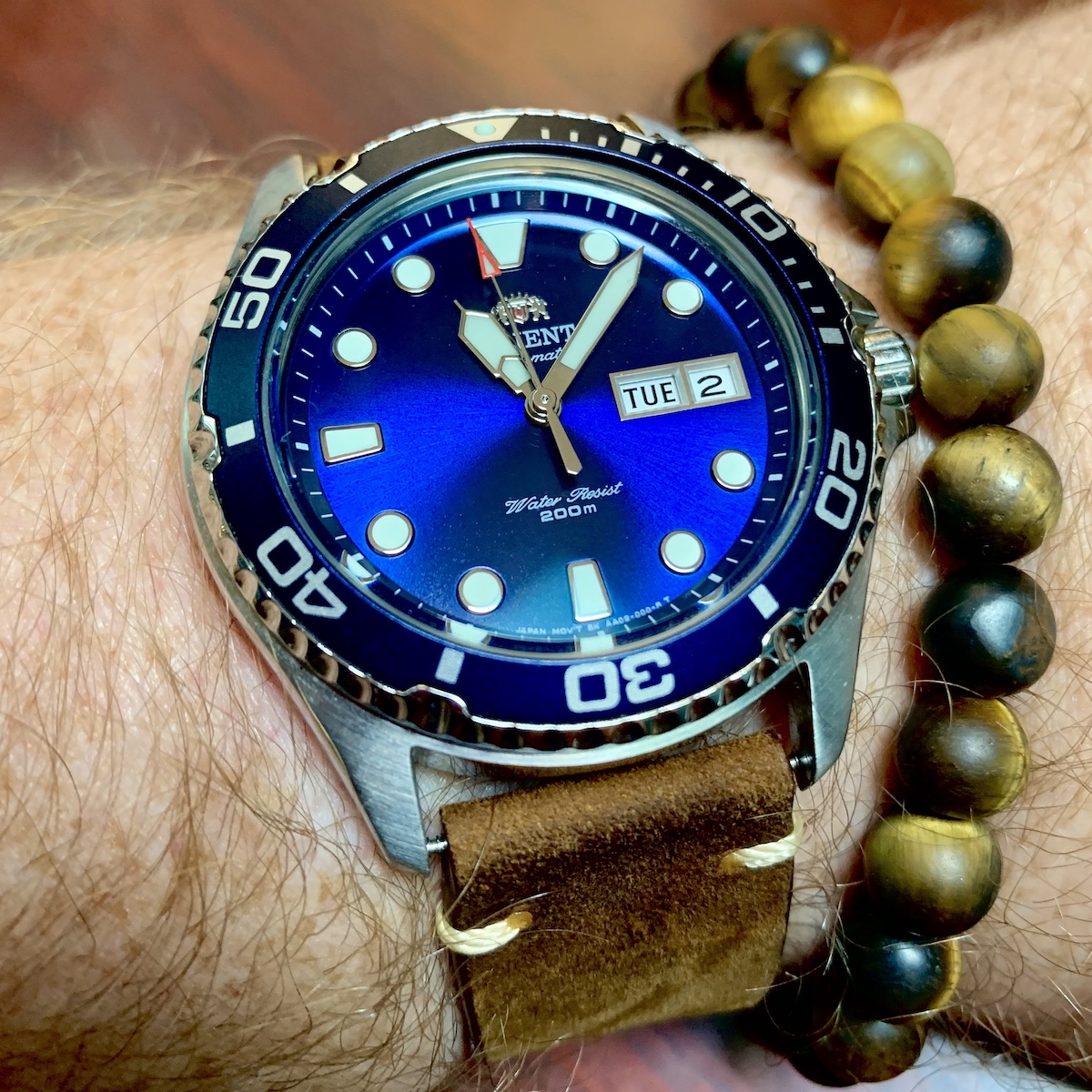An Orient Ray II dive-style watch on a leather strap. The watch features a blue sunburst dial with applied indexes and a day/date complication. The watch case is stainless steel.