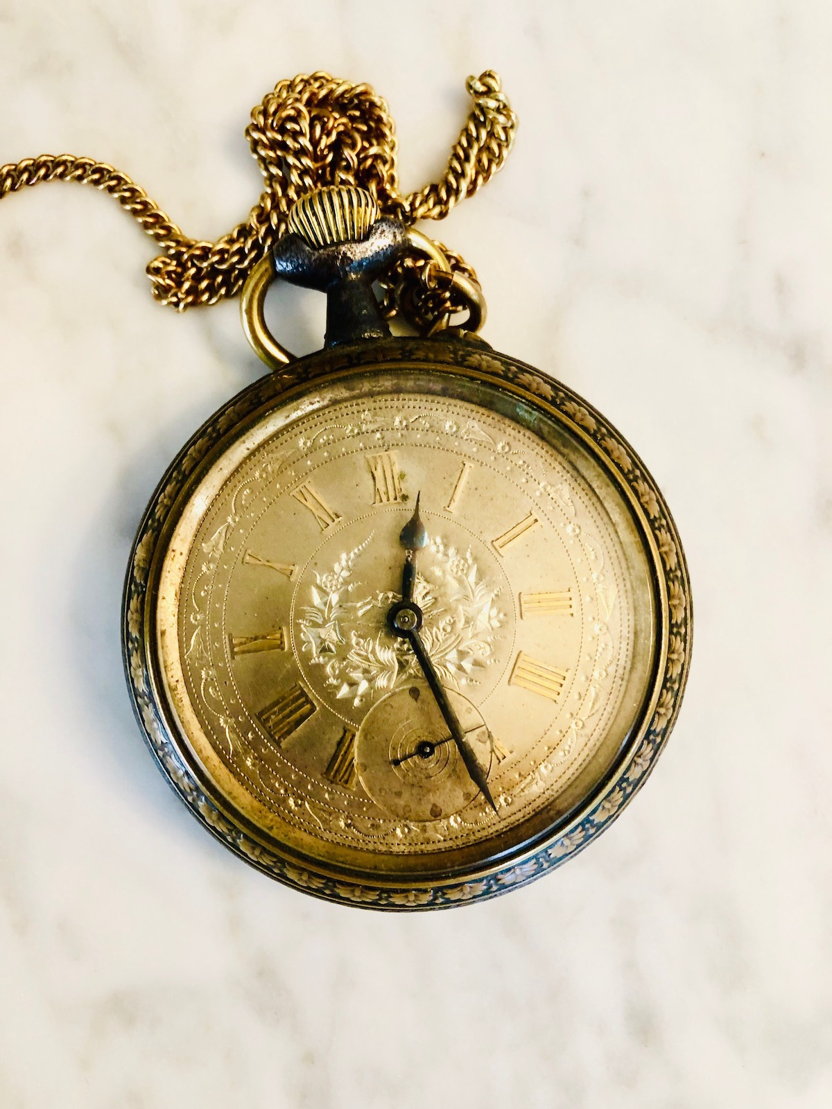 An old pocket watch (roughly 1940), featuring intricate engraving on the dial.