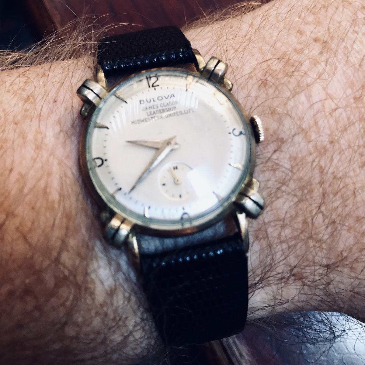 A picture of a 1953 Bulova Jordan watch on my wrist. The watch is gold with a champagne colored face. The watch has a small case (about 34mm) and black , 17mm strap.