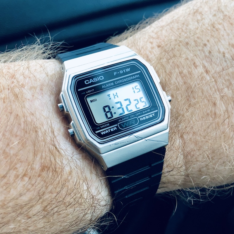 A picture of a slightly scratched Casio brand F-91W watch. The watch features a digital display and 1980's aesthetic.