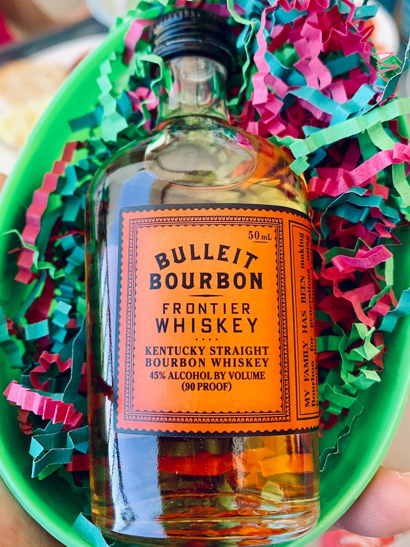 A small bottle of Bulleit Bourbon in a large Easter egg.