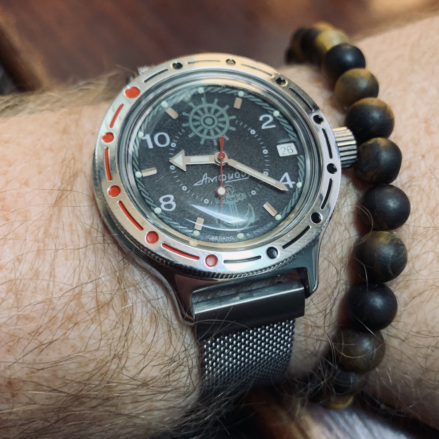 A Vostok Amphibia dive-style watch on a steel mesh strap. The watch features a black dial with a light grey design of a ship's wheel and anchor. The watch case is stainless steel.