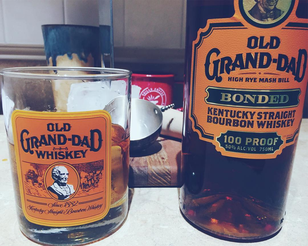 A bottle of Old Grand-Dad bourbon with a matching glass, filled.